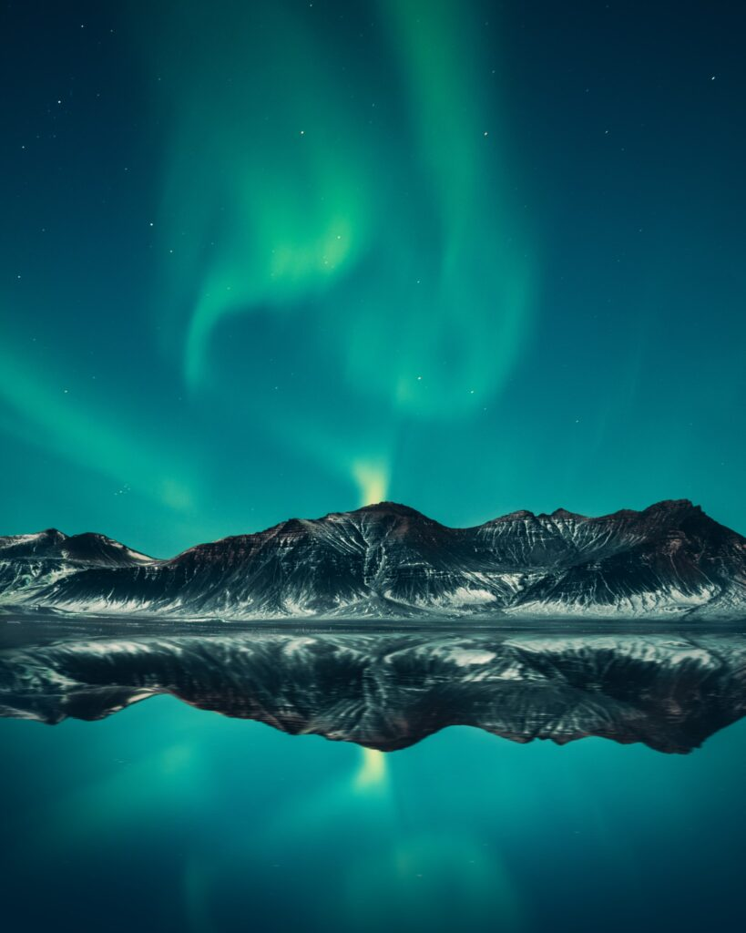 The Northern Lights over mountains and a lake