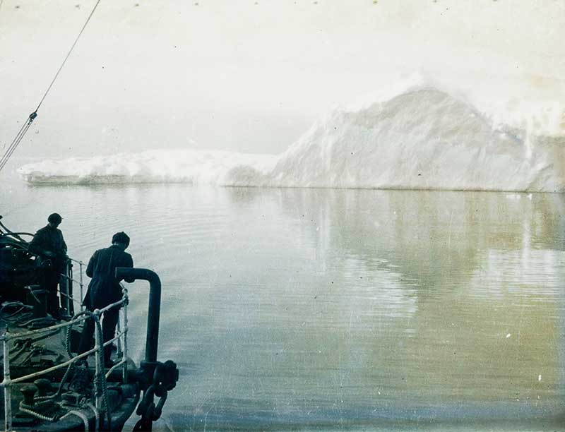 early polar expeditions sail past an iceberg on a ship