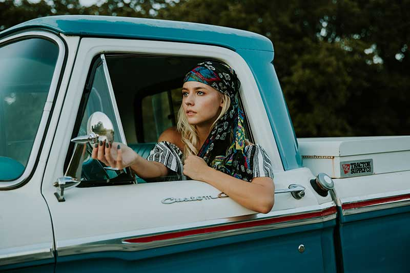 hippy female traveller in classic vintage car.