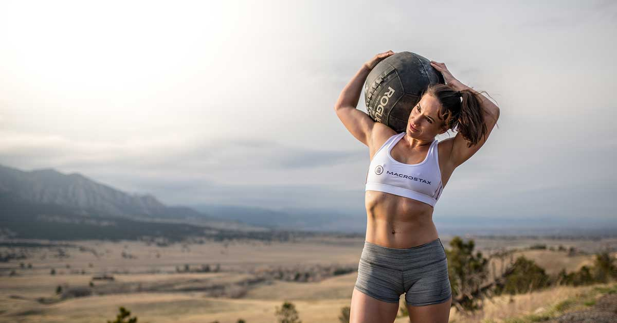 Ground to overhead workouts female athlete outside with D ball in nature