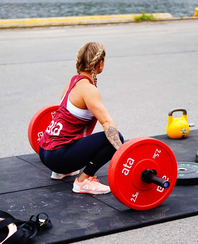 Female athlete training outside with barbell.