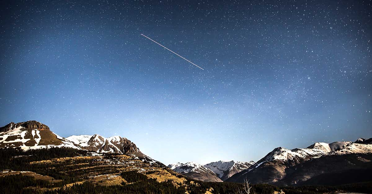 Traveling quotes comet in night sky over mountain range