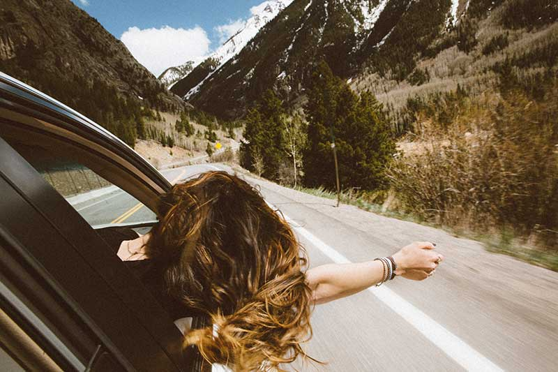 travelling quotes with female explorer in car on road through mountains