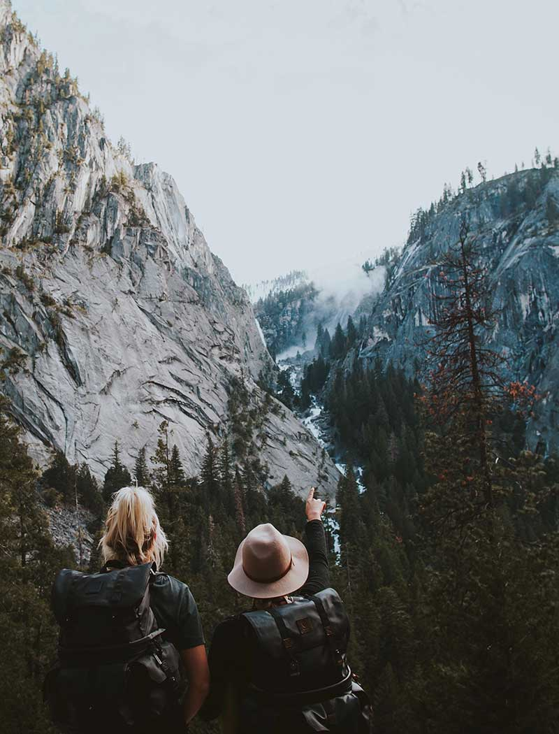 male and female hiker exploring through forest and mountains.