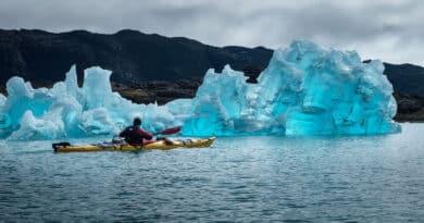 Man in kayak next to iceberg