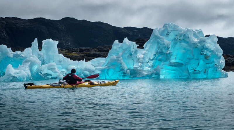 Man in kayak next to iceberg