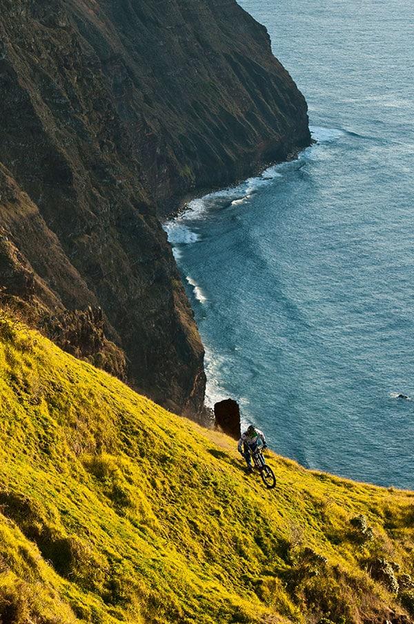 mountain biker on cliff next to the sea