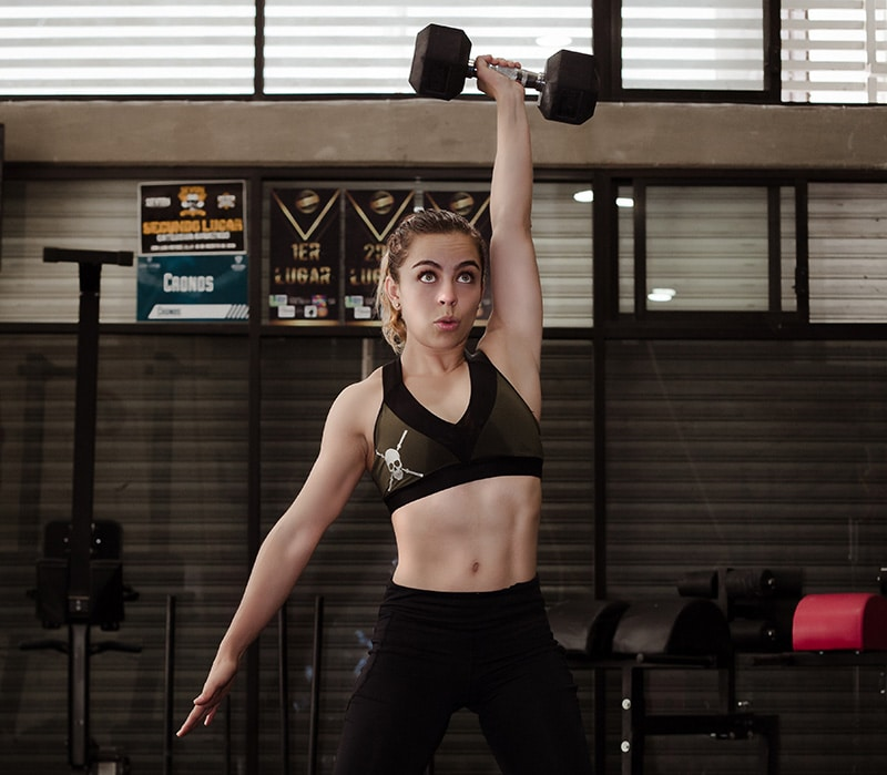 Woman performing a dumbbell snatch in the gym