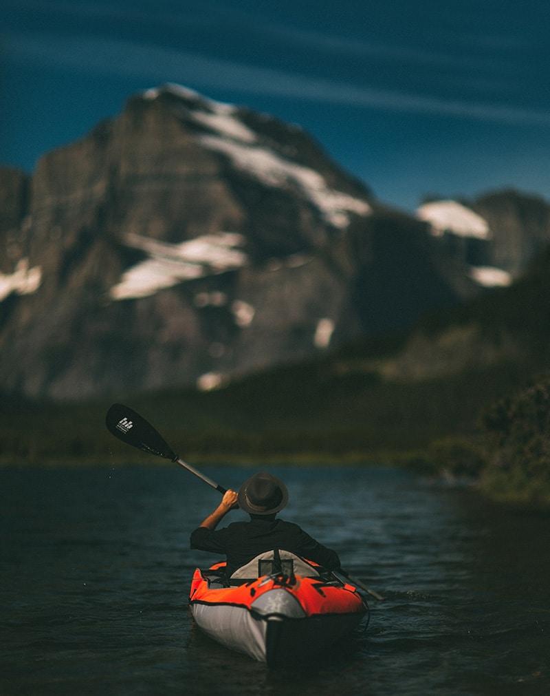 kayaking in a lake next to mountains