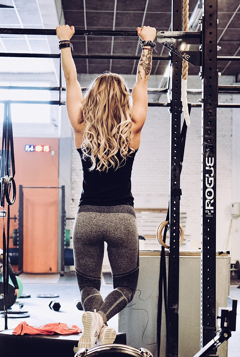 Woman hanging on bar in gym.