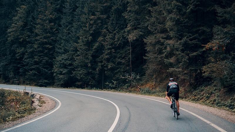 Man cycling near wood.