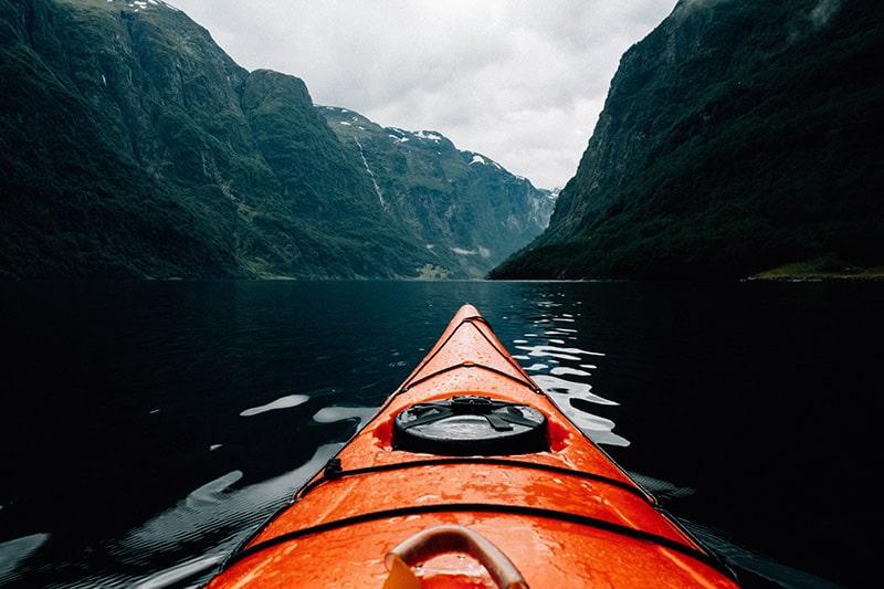 Kayak on dark lake with mountains