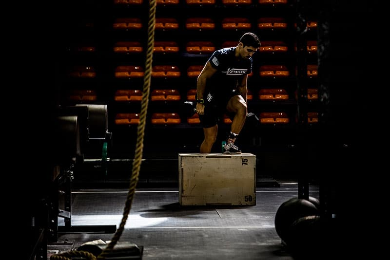 Man performing dumbbell box step overs.