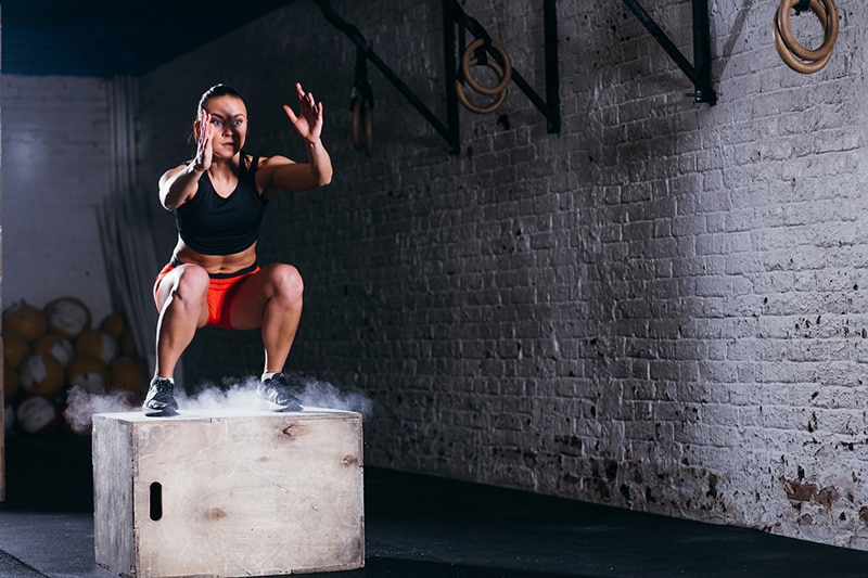 woman in gym on box