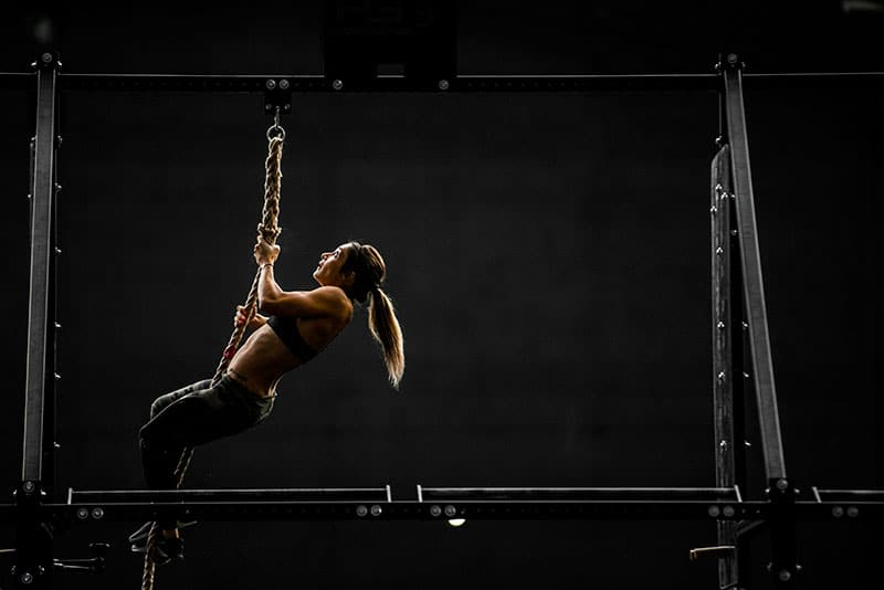 Rope climb during single arm dumbbell snatches workout.