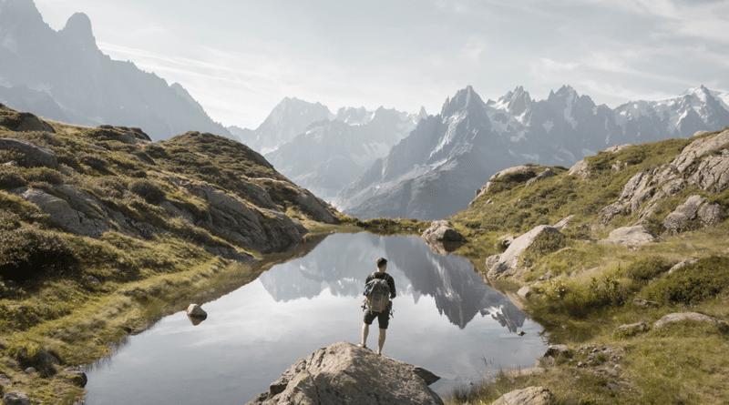 Man outdoors in mountains next to lake adventure