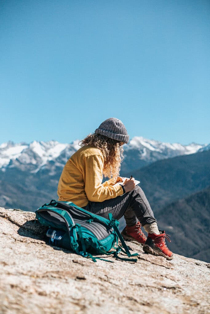 Woman writing while sitting on a rock